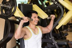 Strong young man exercising for arms muscles at a fitness club w Stock Images
