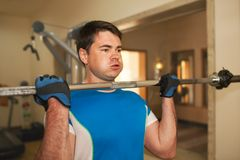 Strong young man exercising with barbell Stock Photography