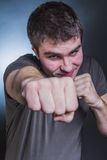 Strong young man in a fighting pose, punching Royalty Free Stock Photo