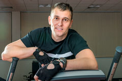 Strong young man at the gym on a simulator Stock Images