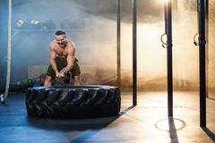 Strong young man hitting wheel tire using hammer in the gym. Strong young man with six abs hitting wheel tire using big hammer in the gym full of smoke and royalty free stock photo