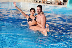 Strong  young man  hugging his girlfriend in a swimming pool Royalty Free Stock Images