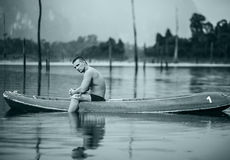Strong young man in kayak on the picturesque lake in Thailand. Royalty Free Stock Photos