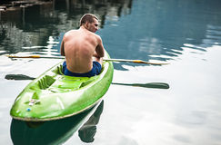 Strong young man in kayak on the picturesque lake in Thailand. Stock Photography