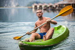 Strong young man in kayak on the picturesque lake in Thailand. Stock Image