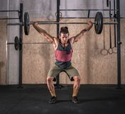 Strong young man lifting bar with weight in the gym stock image