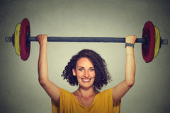 Strong young man lifting barbell above head with two hands Royalty Free Stock Photography