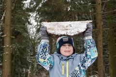 Strong young man lifts heavy piece of wood and holds it Stock Photography