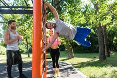 Strong young man practicing human flag exercise with bent legs. Strong and happy young men gripping a vertical bar while practicing human flag exercise with bent Stock Photography