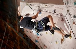 Strong young man pushing himself higher to reach the top of artificial climbing wall in bouldering gym indoors. Motivation healthy sport lifestyle exercise Stock Image