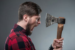 Strong young man with strange sharp hatchet Stock Photo
