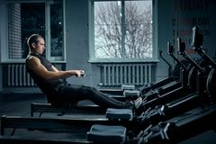 Strong young man in a t-shirt and shorts doing exercises on the simulators in the gym looking to the side stock images