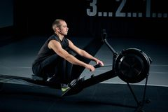 Strong young man in a t-shirt and shorts doing exercises on the simulators in the gym looking to the side royalty free stock photos