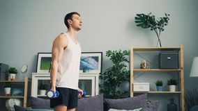 Strong young man training with dumbbells working out arms and shoulders at home stock video footage
