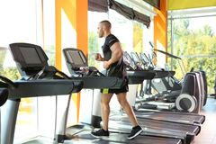 Strong young man on treadmil. L in gym royalty free stock photo