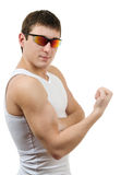 Strong young man in a white t-shirt with sunglasse Royalty Free Stock Image