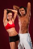 Strong young man and woman with dumbbells Stock Photo