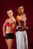 Strong young man and woman with dumbbells Royalty Free Stock Photos