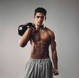 Strong young man working out with kettle bell Stock Photo