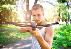 Strong young men with arbalest. Strong young man with arbalest on the wood background Stock Photo