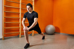 Strong young sportsman in the black sportwear stretching legs before gym workout. Stock Images