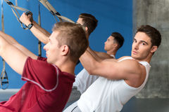 Strong young sportsmen doing push-ups with straps Stock Image