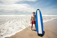 Strong young surf man portrait at the beach with a surfboard. Ba Royalty Free Stock Photo