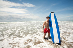 Strong young surf man portrait at the beach with a surfboard. Ba Stock Photography