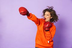 Strong young woman boxer posing isolated over purple background wall wearing boxing gloves royalty free stock photos