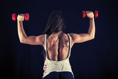 Strong young woman doing dumbbell push press Stock Photography