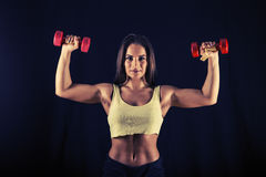 Strong young woman doing dumbbell push press Stock Image
