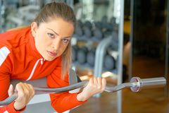 Strong young woman doing exercises with barbell. Fitness, bodybuilding. Health care. stock photo
