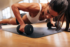 Strong young woman doing push ups. Exercise with dumbbells. Fitness model doing intense training in the gym Stock Image