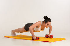 Strong young woman doing push ups exercise with dumbbells. royalty free stock photos