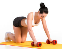 Strong young woman doing push ups exercise with dumbbells. stock photography