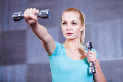 Strong young woman exercising with dumbbells at the gym. Doing shoulder muscles exercise Stock Photography