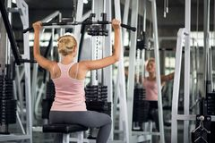 Strong woman exercising with pulldown machine in a fitness club,. Strong young woman exercising with pulldown machine in a fitness club, doing exercises in gym Royalty Free Stock Photos