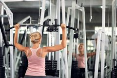 Strong woman exercising with pulldown machine in a fitness club, doing exercises in gym stock photography