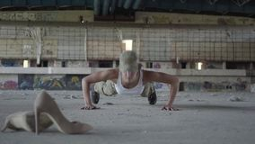 Strong young woman in military uniform wringing herself from the floor on a concrete floor in an abandoned building. A young woman in military uniform wringing stock footage