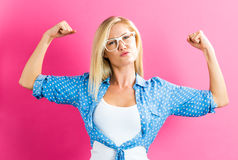 Strong young woman on pink background. Powerful young blonde woman on a pink background Royalty Free Stock Image