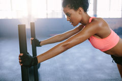 Strong young woman pushing the sled at gym. Side view shot of strong young woman pushing the sled at gym. African woman doing intense physical workout in gym Royalty Free Stock Photo