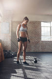 Strong young woman in sportswear at gym. Full length shot of strong young woman in sportswear standing in gym. Tough female athlete at crossfit gym royalty free stock photo