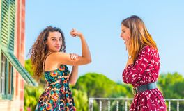 Girl power, hear me roar. Strong young women showing her muscles and physical strength. Girl power, girls are independent and powerful royalty free stock images