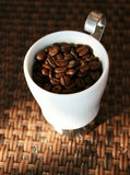 The strongest coffee. Cup of coffe filled with coffee beans Royalty Free Stock Photo