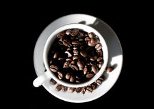 The strongest coffee. Coffee cup filled with roasted coffee beans Stock Images