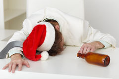 Strongly drunk man in Christmas cap on table Royalty Free Stock Image