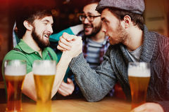Strongman Contest in Irish Pub. Group of drunk men having friendly arm wrestling competition after several glasses of classic craft beer at Irish pub Stock Photography