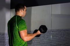 strongman doing dumbbell curls Stock Photo