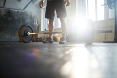 Strongman in Powerlifting Practice. Low section of unrecognizable strong man ready to lift heavy barbell from floor during powerlifting workout in sunlit gym Royalty Free Stock Photography