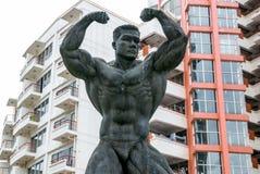 Strongman statue, Bangkok. Statue of strongman flexing muscles, silhouetted, near rajamangala stadium, ramkhamhaeng, Bagnkok Royalty Free Stock Photography